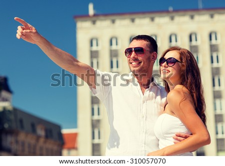 love, travel, tourism, people and friendship concept - smiling couple wearing sunglasses hugging and pointing finger in city