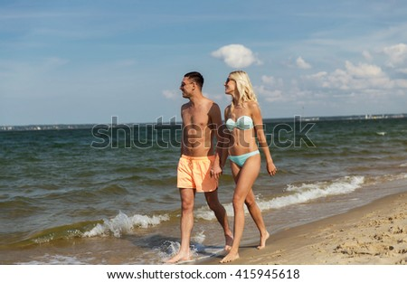 love, travel, tourism, summer and people concept - smiling couple on vacation in swimwear and sunglasses holding hands and walking on beach