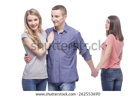 Love triangle. Handsome man embrace his girlfriend while holding hands with another girl. isolated on white background. - stock photo