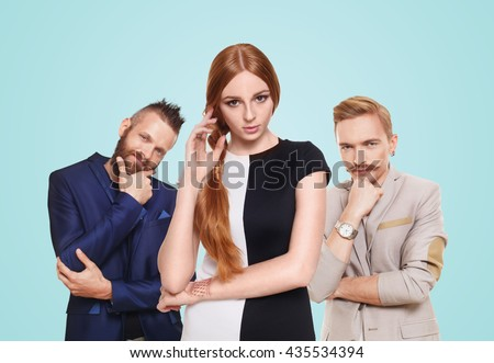 Love triangle. Young beautiful woman choose from to handsome men isolated at blue. Hard choice, lover, husband. Adultery, relationship issue, love problem concept. Girl think who to choose. - stock photo