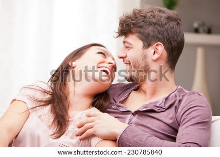love understanding are what this couple shows off while lying on their living room sofa embracing and enjoying - stock photo