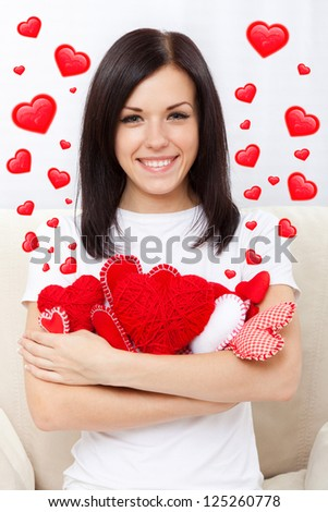 love valentine day woman holding red heart, happy smile girl, sitting on couch at home, valentine's concept hearts flying around - stock photo