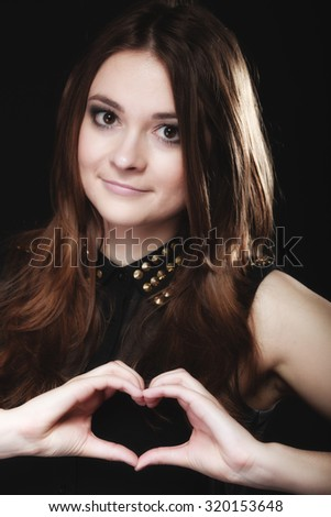 Love valentine's day concept. Woman teen girl doing forming heart shape love symbol with her hands on black - stock photo