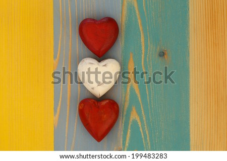 Love Valentine's red and white wooden hearts on painted board texture background, copy message space