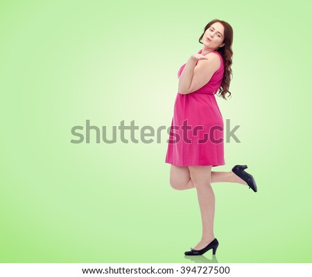 love, valentines day and people concept - happy young plus size woman posing in pink dress and sending blow kiss over green natural background