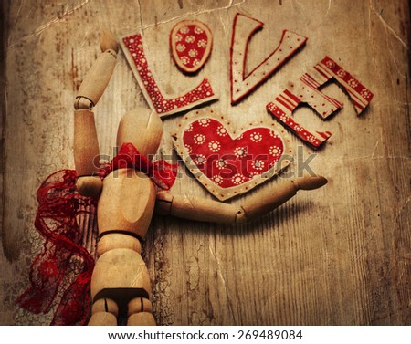Love valentines day background, wooden man with red bow on his neck dancing, holding red heart on wooden table background. - stock photo
