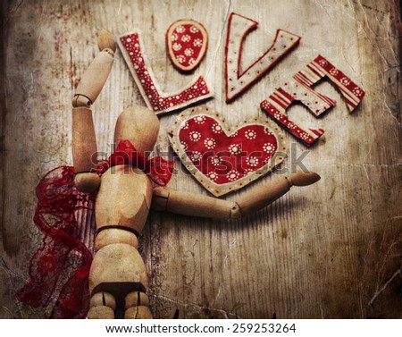 Love valentines day background, wooden man with red bow on his neck dansing, holding red heart on wooden table background - stock photo