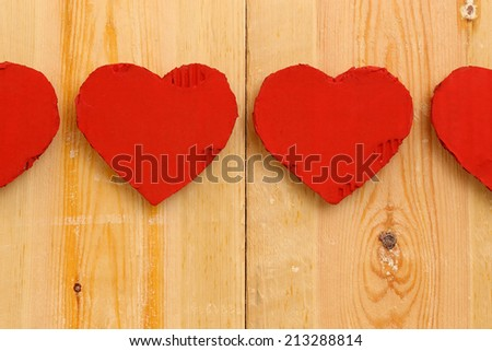 Love Valentines red painted recycled cardboard hearts on rough sawn pine boards background, copy space - stock photo
