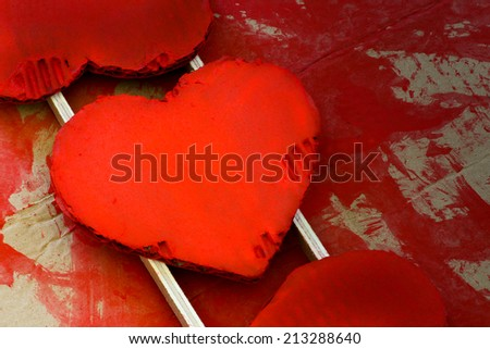 Love Valentines red painted recycled cardboard hearts on working rough paint background, copy space - stock photo