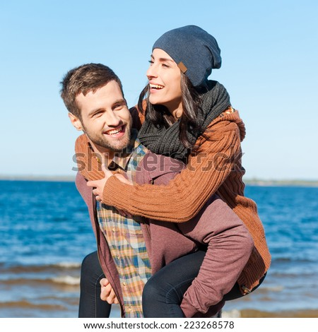Love with no regrets. Beautiful young loving couple having fun while walking by the beach  - stock photo