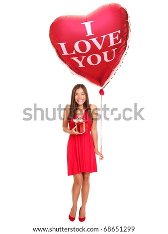 Love woman holding valentines day gift and heart balloon saying ?I love you?. Beautiful young woman smiling in red dress. Asian / Caucasian female model isolated on white background in full length. - stock photo