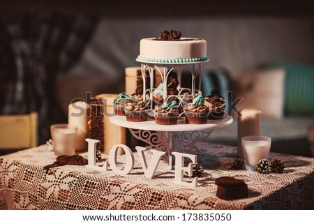 LOVE wooden letters on a holiday decorated table with candles and cupcakes - stock photo