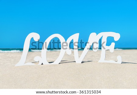 Love word at sea beach sand against waves background, St.Valentines day traveling or greeting card concept