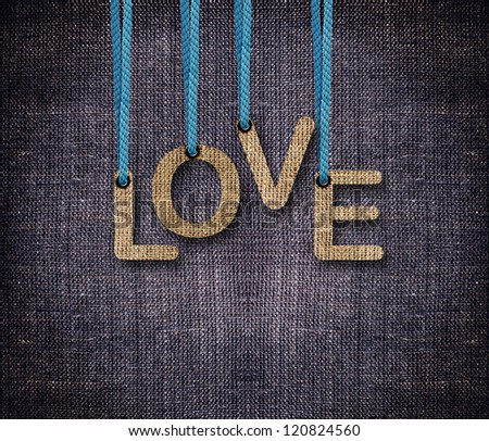 Love word hanging by rope as puppeteer on sackcloth background. - stock photo