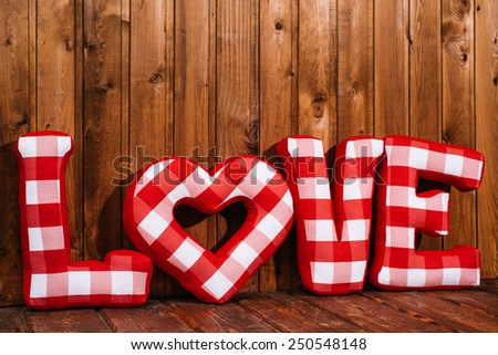 Love word of plush red letters on wood background. Full plaid textile. February 14, Valentine's Day concept shot with text space. Front view. High resolution - stock photo