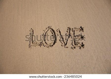 love word written on brown sand ground low tide beach ocean seashore in Spain Europe - stock photo