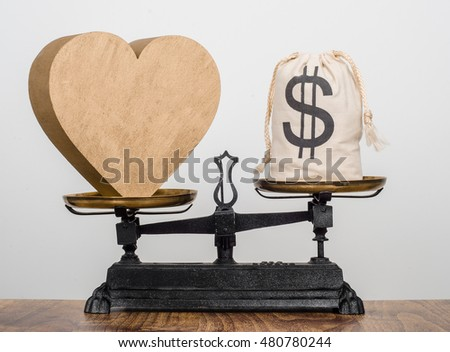 Love worth more than money. A heart heavier than a bag full of money on antique balance scales.