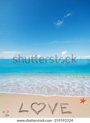 love written on a tropical beach under clouds - stock photo