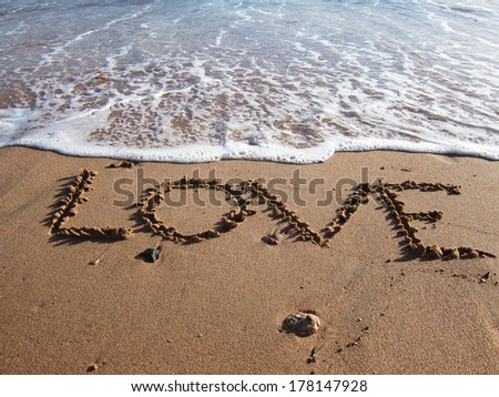 Love written on the sand slowly being washed up by the rising tide - stock photo