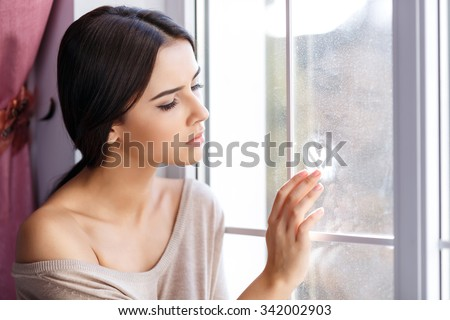 Love you so much. Pleasant sullen cheerless beautiful girl sitting on the window sill and painting on glass while waiting for her love heart