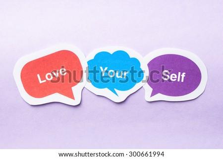 Love your self concept paper bubbles against purple background. - stock photo