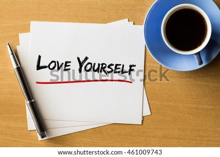 Love yourself - handwriting on papers with cup of coffee and pen, love concept