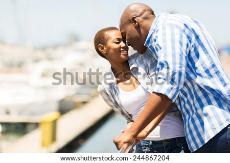 lovely african american couple kissing at the harbour - stock photo