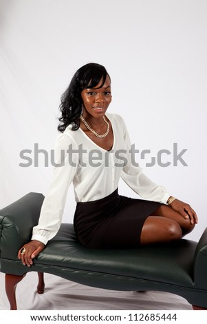 Lovely African American woman  in a white blouse and black skirt, sitting and looking at the camera with a happy, friendly expression and a smile