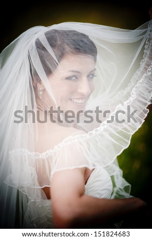 Lovely and happy brunette bride posing outdoor