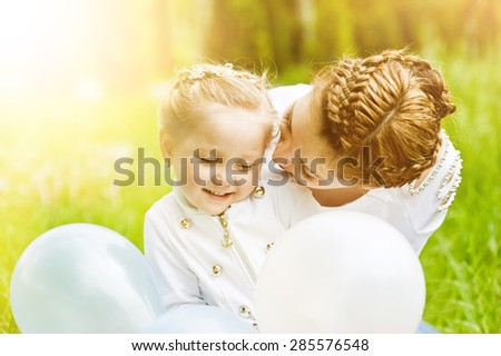 Lovely and sweet girl with balloons hugging her mother in a park a sunny summer day. - stock photo