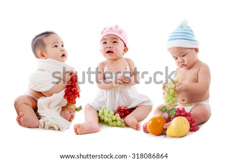 Lovely asian babies sitting on the floor with fruits - stock photo