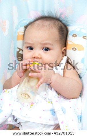 lovely asian baby with milk bottle in mouth