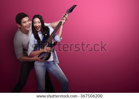 Lovely asian couple playing guitar. Valentine day concept - stock photo