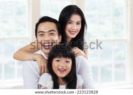 Lovely asian family laughing together at camera in the home - stock photo