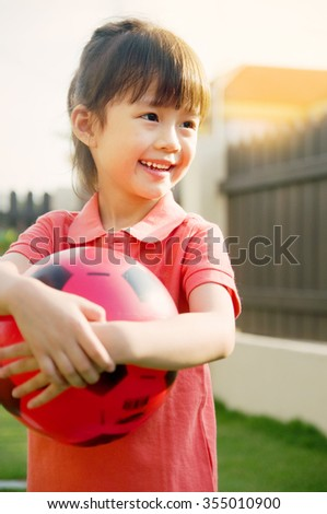Lovely asian girl playing ball - stock photo