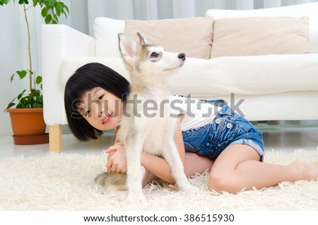 Lovely asian girl playing with dog in the living room