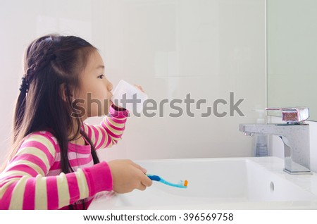 Lovely asian girl rinse her mouth after brushing her teeth - stock photo