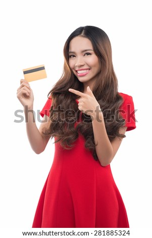 Lovely asian woman holding showing credit card smiling happy in red dress. Young female professional showing empty blank credit card sign smiling happy at camera. Beautiful Asian Caucasian model. - stock photo
