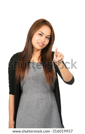 Lovely Asian woman in black sweater with light brown hair looking at camera with raised index finger pressing, interacting imaginary button or touchscreen interface. Thai national of Chinese origin