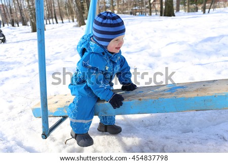 lovely baby age of 1 year on old seesaw outdoors in winter