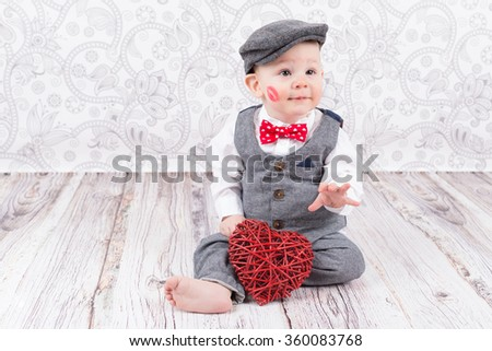 lovely baby boy in barret with lipstick kiss on his cheek and red heart - stock photo