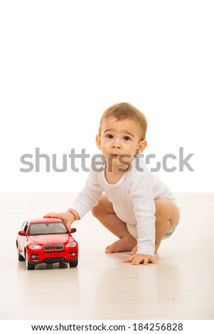 Lovely baby boy playing with a big car toy on floor
