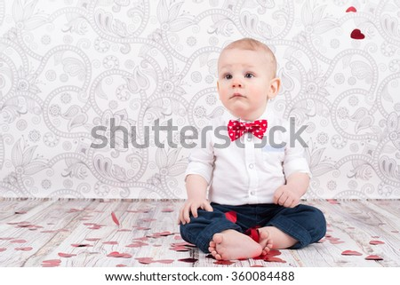 Lovely baby boy sitting among glittering red hearts