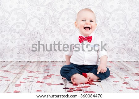 Lovely baby boy sitting and smilling among glittering red hearts - stock photo