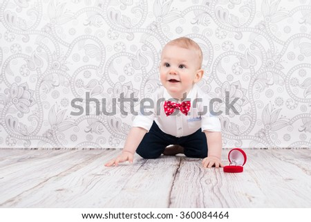 Lovely baby boy smilling and pose with betrothal ring - stock photo