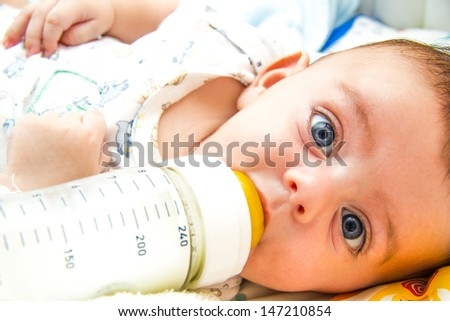 Lovely baby feeding on milk bottle - stock photo