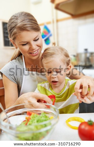 Lovely baby girl helping mother with meal in the kitchen. Young smiling female with little daughter cooking vegetables for family dinner.