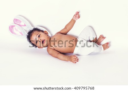 Lovely baby girl portrait lying and wearing bunny ears - stock photo