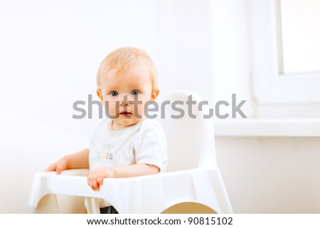 Lovely baby sitting in baby chair - stock photo