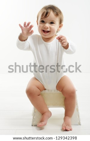 Lovely baby sitting in chair - stock photo
